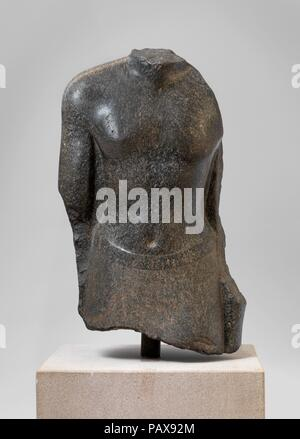 Torso of an official of Nectanebo I. Dimensions: H. 43.5 x W. 23.8 x D. 13.5 cm (17 1/8 x 9 3/8 x 5 5/16 in.). Dynasty: Dynasty 30. Reign: reign of Nectanebo I. Date: 380-362 B.C..  The name of the man represented is not preserved, but he proudly asserts his attachment to Nectanebo I by placing the king's cartouches at the head of the texts on the back pillar. The slightly greenish flocked stone is associated with the site of Saft el-Hina, and, indeed, the left side of the back pillar figures an address by the deceased to the priesthood of the temple of Sopdu, confirming that the statue stood  - Stock Photo