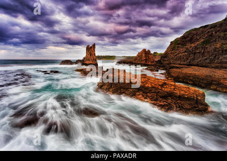 Colourful golden sandstone cathedral rocks at Bombo beach in Kiama, NSW, Australia, at stormy sunset under cloudy sky. - Stock Photo