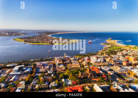 Delta of Hunter river at Newcastle city CBD behind Nobbys head via developed industrial and residential waterfront in aerial elevated view. - Stock Photo