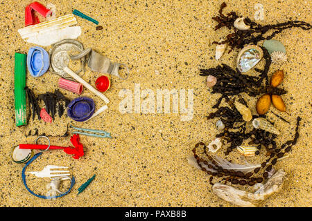 Real plastic pollution found on beach separated and sorted from natural beach seaweed and shells where it was found, space for text - Stock Photo