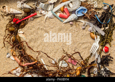 Real plastic pollution found on beach mixed in with natural seaweed and shells where it was found, space for text - Stock Photo