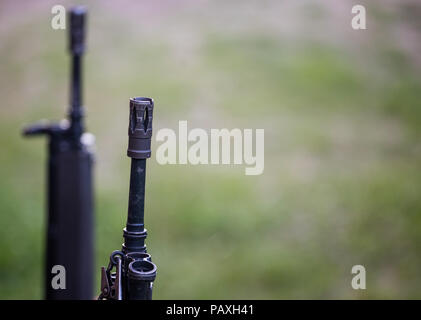 Firearm handgun. Front side of weapon with close up view on blurred nature background. - Stock Photo