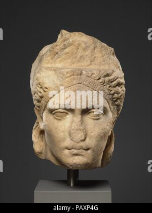 Over-life-sized marble portrait, probably of the empress Sabina. Culture: Roman. Dimensions: 14 3/4 in. (37.5 cm). Date: ca. A.D. 121-128.  This imposing head probably comes from a statue of Sabina, wife of the emperor Hadrian. The face was originally surmounted by a very high, ovoid hairpiece covered with small curls, a style that was fashionable at the court of Trajan in about A.D. 100.  The upper part of the hairpiece was carved separately and added onto the shelf-like area above the forehead. In back, the hair is arranged like that of a classical statue of Venus, goddess of love, with long - Stock Photo