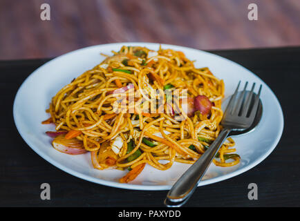 Chinese Noodles, Chowmein on a Plate with Spoon and Fork,Hot and Fresh Chow Mein in Nepali Style - Stock Photo