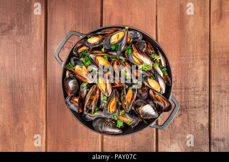 A full skillet of marinara mussels, shot from above on a dark rustic background with copy space - Stock Photo
