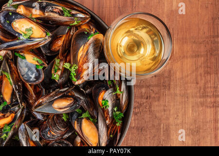 A full skillet of marinara mussels, shot from above on a dark rustic background with wine and copyspace - Stock Photo