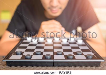 Strategic Planning, Man wear black shirt playing checkers game - Stock Photo