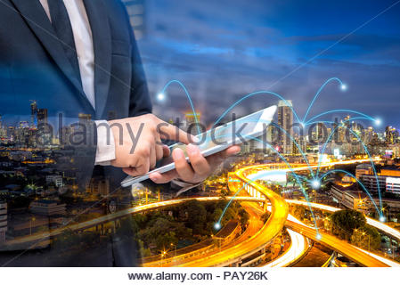 Double exposure businessman using digital tablet at urban with symbol internet link connection, Work anywhere anytime concept. - Stock Photo