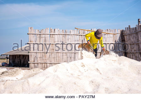 Worker is working in sea salt field at Samut Songkhram,Thailand. Salt production is made from sea water and sunlight until dry. - Stock Photo