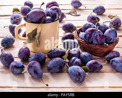 Blue large plums juicy sweet fruit for dietary nutrition lie in a yellow metal mug and in a wicker basket on a plank background - Stock Photo