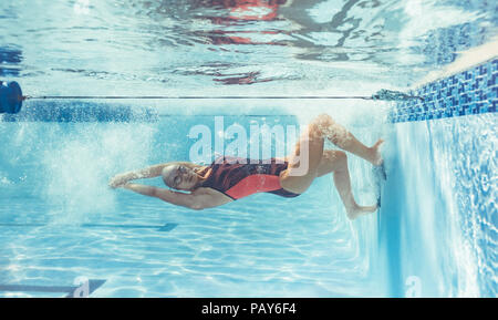 Shot of professional swimmer turning over underwater while swimming. Female swimmer in action inside pool. - Stock Photo