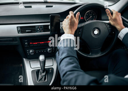 Rear view of man in formal clothes holding the steering wheel of his car with both hands. Businessman driving car with mobile phone clipped to dashboa - Stock Photo
