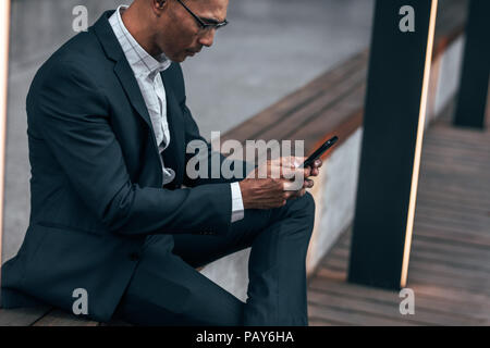 Entrepreneur typing text in mobile phone sitting on side railing outdoors. Businessman sitting outdoors managing work using cell phone. - Stock Photo