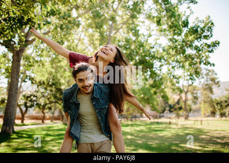 Handsome young guy giving his girlfriend a piggyback ride at park. Couple piggybacking outdoors. Man carrying woman with wide spread arms. - Stock Photo