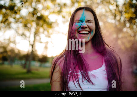 Portrait of a smiling young woman with face smeared with colors. Cheerful girl at park with colored powder on her face. - Stock Photo
