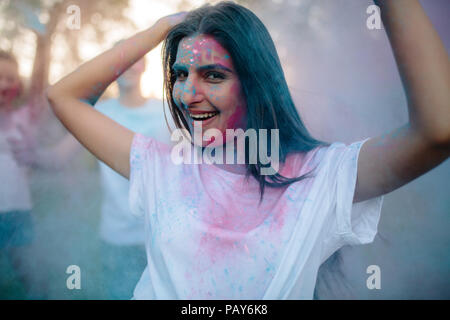 Happy young woman partying under colorful powder cloud with her friends at the back. Woman enjoying festival of colors with friends. - Stock Photo