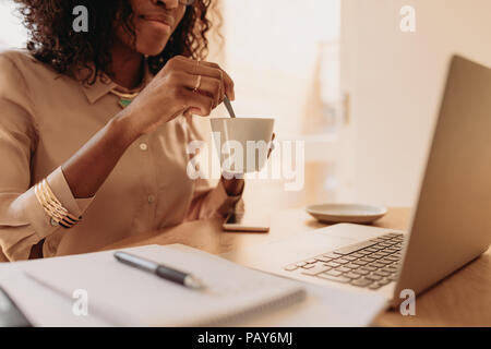Businesswoman working on laptop computer sitting at home holding a coffee cup in hand. Woman entrepreneur stirring her coffee with spoon while working - Stock Photo