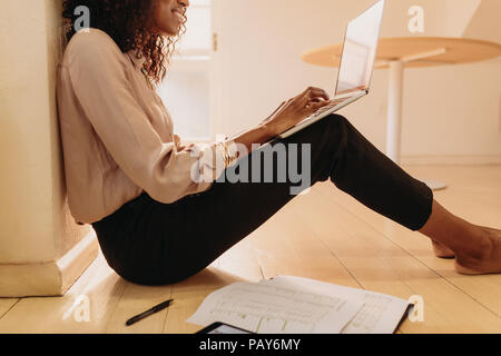 Side view of a woman entrepreneur in formal attire working on laptop computer sitting at home. Businesswoman sitting on floor at home working on lapto - Stock Photo