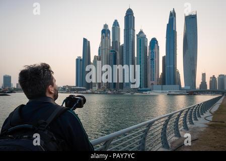 DUBAI, UAE - February 15, 2018: Tourist admire tallest buildings of Dubai Marina waterfront in Dubai, UAE - Stock Photo