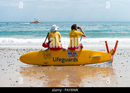 Under a blue summer sky the ladies of the Tenby RNLI Lifeguards watch over holidaymakers on Castle Beach in the pretty seaside town of Tenby. - Stock Photo