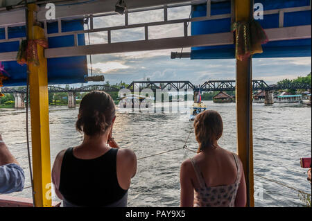 Tourists on a boat floating towards the bridge over the river Kwai. Kanchanaburi. Thailand - Stock Photo