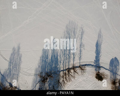 winter time tree shadows on lake ice, aerial view - Stock Photo