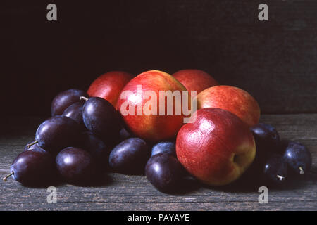 Fresh nectarines and plums or damsons on a dark wooden background, copy or text space - Stock Photo