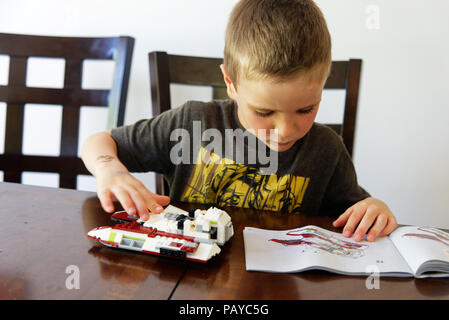 A young boy (6 yr old) concentrating on making his Lego Star Wars fighter - Stock Photo