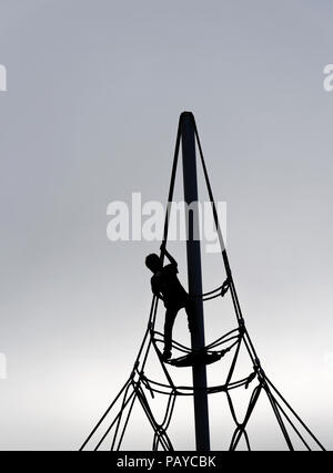 A silhouette of a young boy (6 yr old) on a rope climbing frame - Stock Photo
