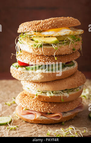variety of sandwiches on bagels: egg, avocado, ham, tomato, soft cheese, alfalfa sprouts - Stock Photo