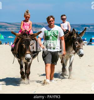 Donkey ride on the beach at Weymouth, Dorset, UK. - Stock Photo