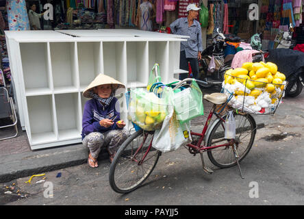 Vietnamese woman street vendor sitting on the curb by her bicycle loaded with mangoes in Ho Chi Minh City, Vietnam. - Stock Photo