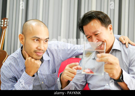 Two asian guys are seeing betta fish in the glass and very happy - Stock Photo