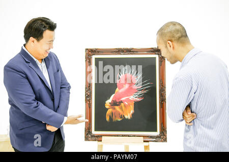 Two Asian men are seeing the beautiful siamese fighting fish (betta) photo in the museum exhibition. - Stock Photo