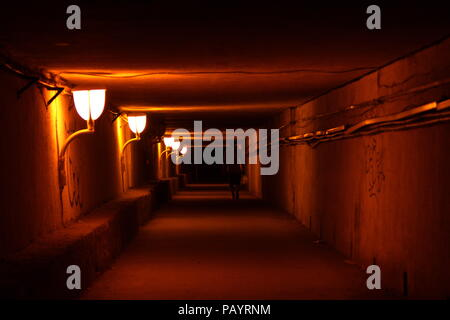Silhouette of a man walking through the passage lighted by lanterns - Stock Photo