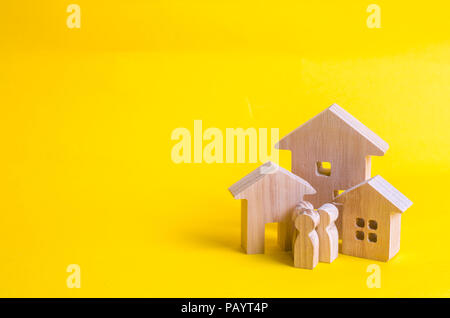 Wooden houses and people on a yellow background. The concept of buying home sales, rent. Construction and relocation. Adaptation in the new city. Inve - Stock Photo