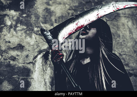 Witch licking blood on reaper. Female demon angel in black clothes and hood on grunge wall background. Halloween day and Mystery concept. Fantasy of m - Stock Photo