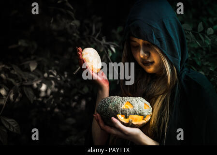 Witch opening pumpkin lid by hand. Old woman holding bright pumpkin in dark forest. Halloween day and Mystery concept. Fantasy of magic theme. Demon a - Stock Photo