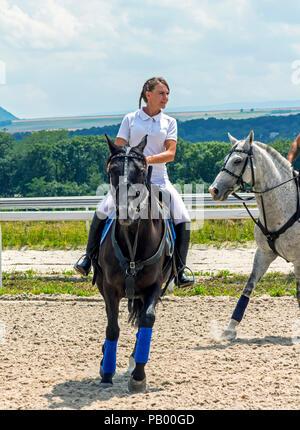 PYATIGORSK, RUSSIA - JULY 22, 2018:Beautiful women show elements of jiggery, riding a brown horse on racecourse Pyatigorsk. - Stock Photo