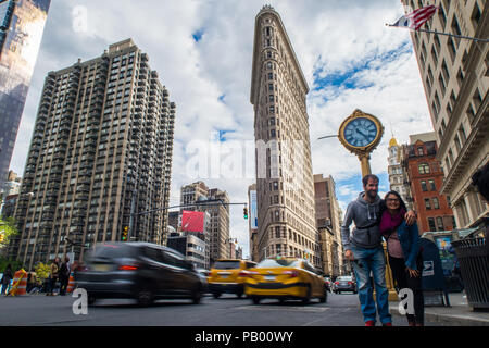 A tourist couple have their photograph taken in front of the Flat Iron Building, New York, United States of America - Stock Photo