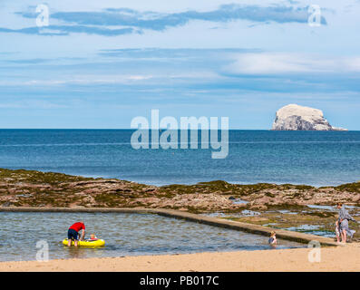 Young children in inflatable rowing boat in outdoor tidal bathing pool with Bass Rock, Milsey Bay, North Berwick, East Lothian, Scotland, UK - Stock Photo