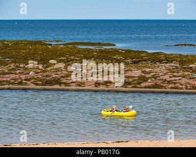 Young children in inflatable rowing boat in outdoor tidal bathing pool with Firth of Forth, Milsey Bay, North Berwick, East Lothian, Scotland, UK - Stock Photo