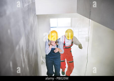 Woman and man workers running up the stairs at the construction site. - Stock Photo