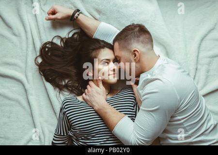 Portrait of beautiful romantic young couple man woman in love hugging, kissing, lying on floor on white rug carpet indoors at home, toned with filters - Stock Photo