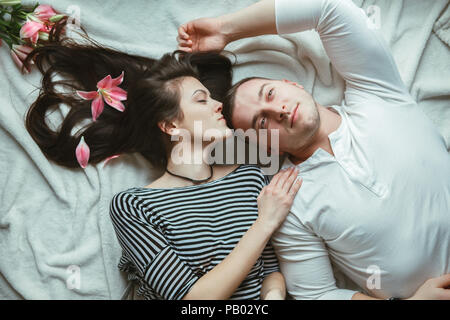 Portrait of beautiful romantic young couple man woman in love hugging, kissing, lying on floor on white rug indoors at home surrounded with pink lily  - Stock Photo