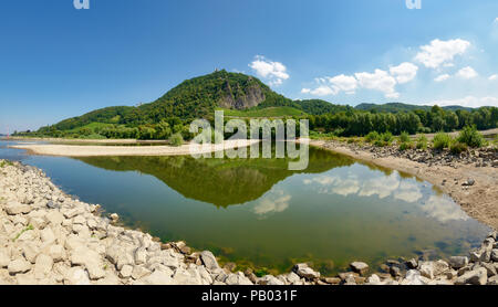 Panoramic view of the hill Drachenfels in Siebengebirge with mirror imaging in the water of river Rhine with low water level between groins, Germany - Stock Photo
