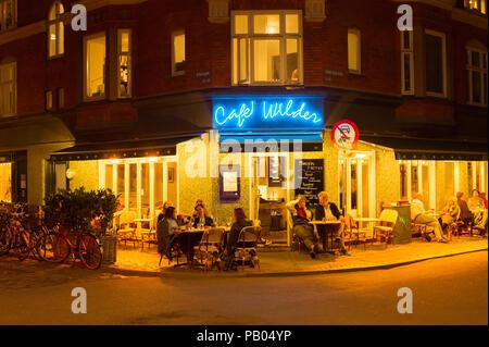 COPENHAGEN, DENMARK - JUNE 16, 2018: People at a street restaurant in Copenhagen. Copenhagen is the capital of Denmark - Stock Photo