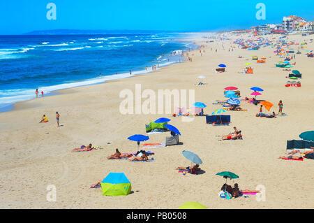 ESPINHO, PORTUGAL - JUL 30, 2017: People sunbathe at the ocean beach. Portugal famous tourist destination for it's ocean beaches. - Stock Photo