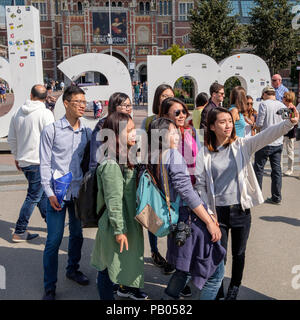 Tourists taking a selfie in front of the iAmsterdam sign at the Museum Square in Amsterdam. - Stock Photo