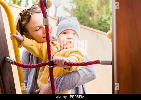Mom and son climb the net of cables on the playground